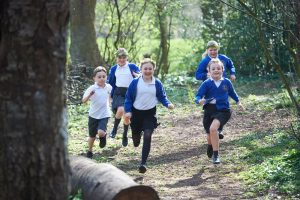 children running through forest